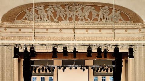 Ein ganzer Kinderreigen im reich gestalteten Korbbogenfeld über der Bühne verbildlicht die unterschiedlichen Formen der darstellenden Kunst, welche im Theater Casino Zug seit 110 Jahren Platz haben.