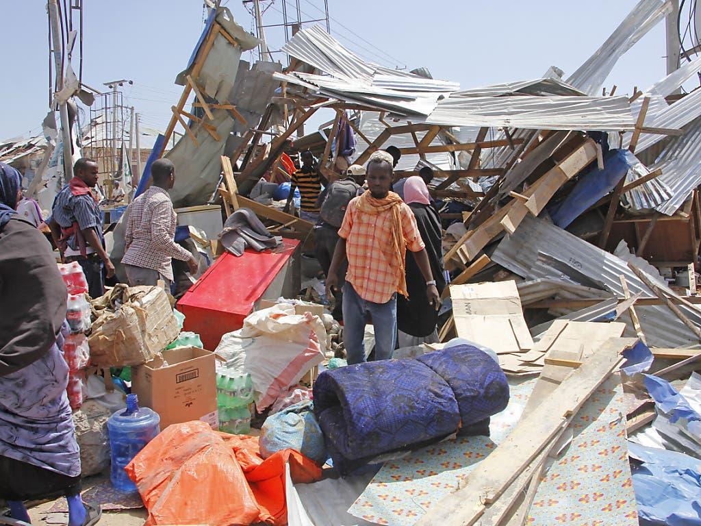 Menschen versuchen Waren aus Läden zu retten, die durch den verheerenden Sprengstoffanschlag zerstört wurden.