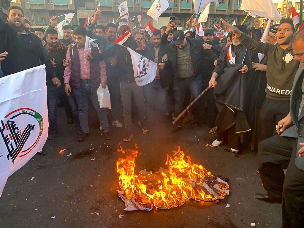 Die Demonstranten verbrennen vor der US-Botschaft in Bagdad US-Flaggen. Zudem zertrümmerten sie Fenster und rissen Überwachungskameras aus den Wänden.