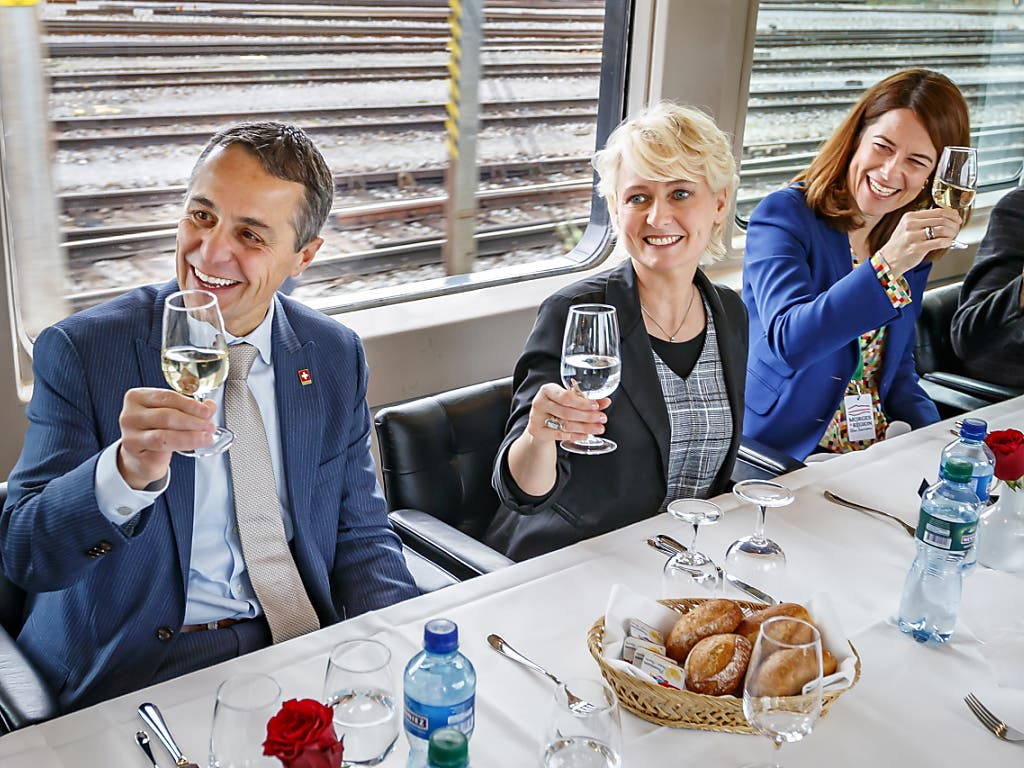 Isabelle Moret (Bildmitte), Bundesrat Ignazio Cassis und FDP-Parteipräsidentin Petra Gössi prosten im Zug den anderen Gästen zu, welche zur Wahlfeier ins Waadtland mitreisen.