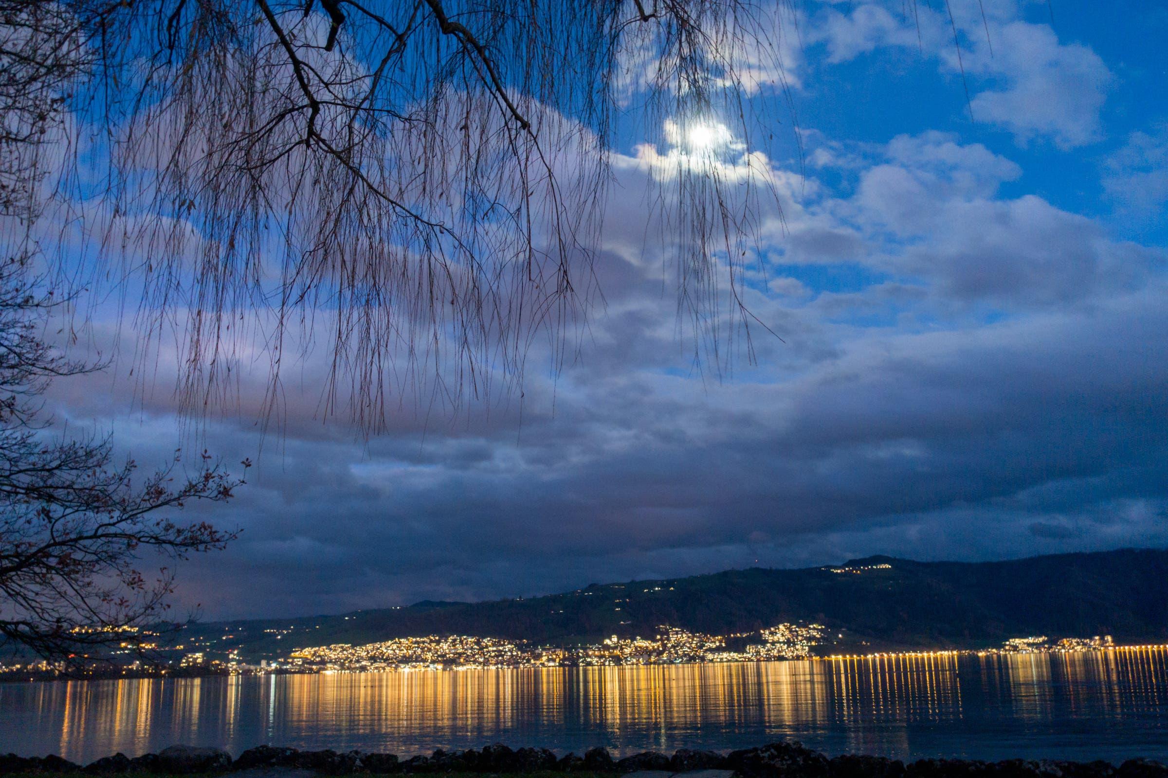 Einnachten über dem Zugersee mit zunehmendem Halbmond und reflektierenden Lichtern der Stadt.