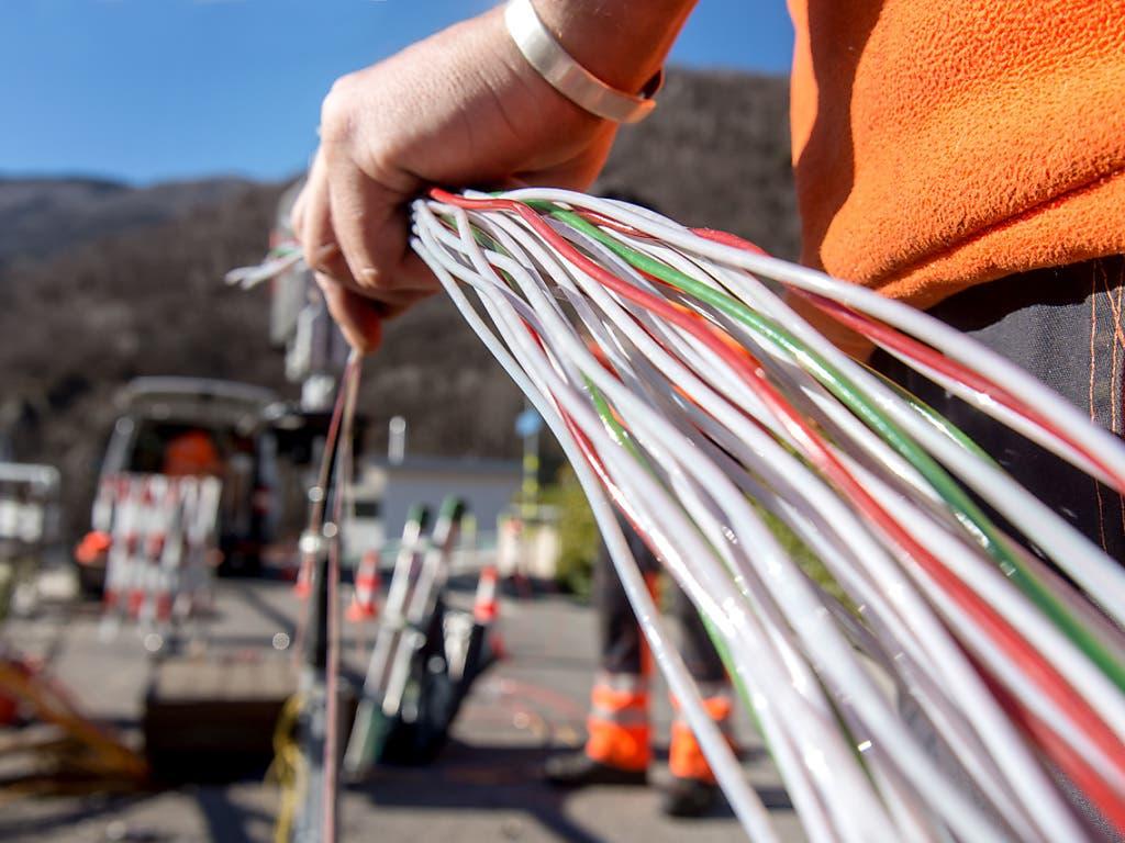 Ein Arbeiter montiert Glasfaserkabel der Swisscom. Die Comcom stützt sich bei der Preisberechnung für die Mitbenützung des Swisscom-Netzes neu auf die Kosten für Glasfaserleitungen. (Bild: KEYSTONE/TI-PRESS/CARLO REGUZZI)