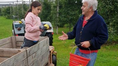 Ein Senior gibt einem Mädchen in Güttingen sein Wissen über den Obstbau weiter. (Bild: PD)