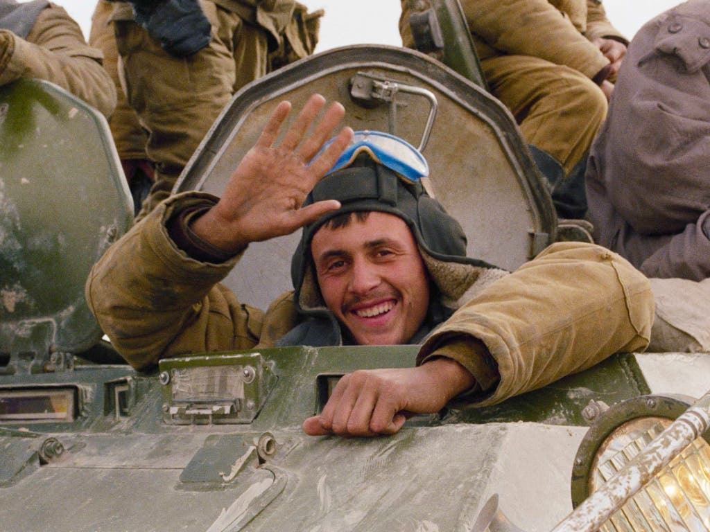 Mit einem Lächeln winkt ein sowjetischer Soldat am 7. Februar 1989 beim Abzug seiner Einheit aus Afghanistan aus Hayratan. Am Freitag gedachten in Moskau hunderte Veteranen des Abzugs. (Archivbild/KEYSTONE/AP Photo/Boris Yurchenko) (Bild: KEYSTONE/AP/BORIS YURCHENKO)