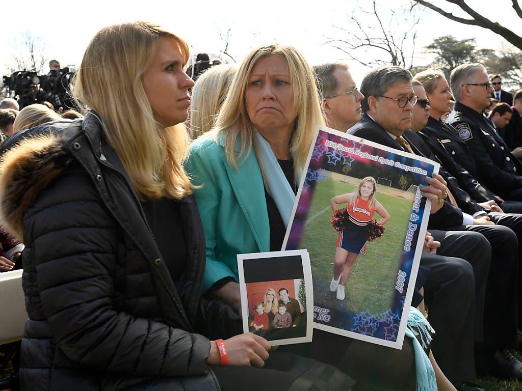 Zwei Zuhörerinnen an US-Präsident Trump Notstandsrede mit Fotos von Familienmitgliedern, die von Gewalt durch illegale Immigranten betroffen waren. (Bild: KEYSTONE/AP/SUSAN WALSH)