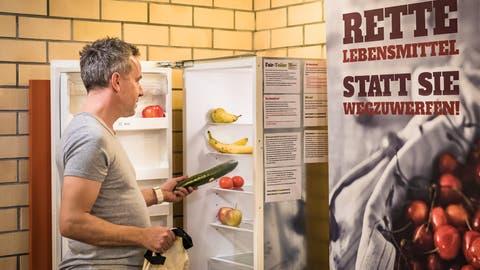 Thomas Leuthard, Vorstandsmitglied von Foodsharing Zug, befüllt einen der Kühlschränke. (Bild: Christian H. Hildebrand (20. Februar 2019))