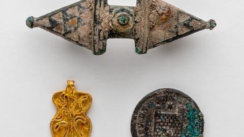 In Altdorf gefunden: eine römische Gewandspange (oben), eine römische Münze des Kaisers Constantinus (rechts) und ein goldener Anhänger aus dem 6./7. Jahrhundert (links). Bild: F.X. Brun, Altdorf, Februar2019)
