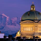 The Federal Palace pictured during the sunset with a beautiful view of the Alps, in Bern, Switzerland, Wednesday, February 13, 2019. (KEYSTONE/Anthony Anex)