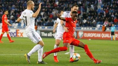 2:0-Torschütze Denis Zakaria (in Rot) kämpft um den Ballbesitz – links Ex-FC-Luzern-Spieler Valerian Gwilia. (Bild: Zurab Kurtsikidze/Keystone,Tiflis, 23. März 2019)