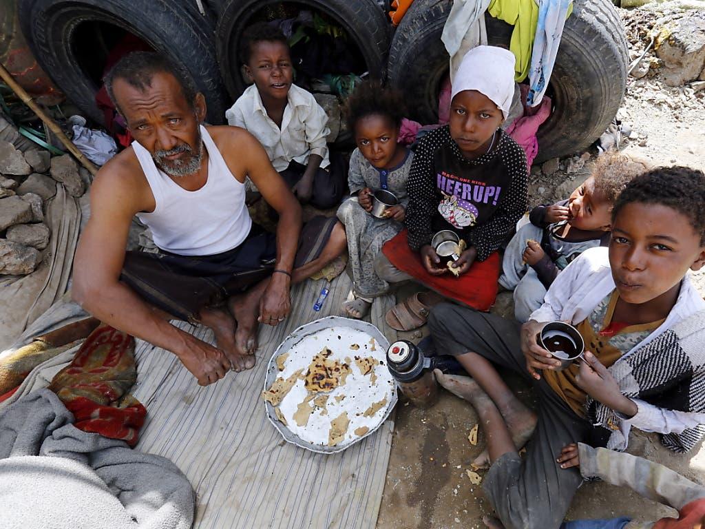 Jemenitische Bürgerkriegsopfer teilen sich eine Mahlzeit im behelfsmässigen Unterstand. (Bild: KEYSTONE/EPA/YAHYA ARHAB)
