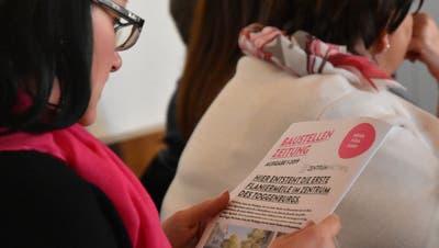 Eine Teilnehmerin am Zentrum-Znüni begutachtet einen ersten Entwurf der Baustellenzeitung. (Bild: Ruben Schönenberger)