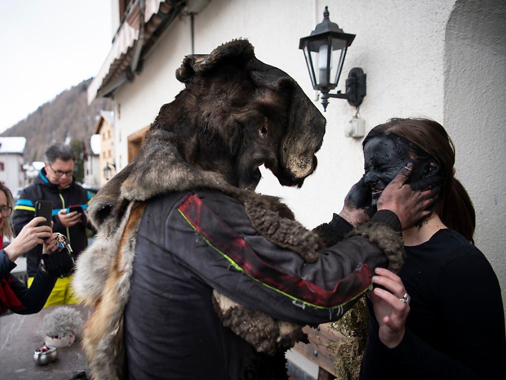 Ein Pschuurirolli schwärzt einer Frau in Spluegen. das Gesicht. (Bild: KEYSTONE/GIAN EHRENZELLER)