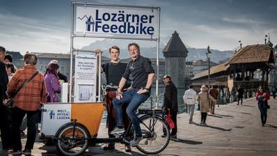 André Bachmann und Philippe Stutz (links) von der IG Weltoffenes Luzern auf dem Velo mit integriertem Briefkasten am Rathausquai. (Bild: Pius Amrein,Luzern, 1. April 2019)