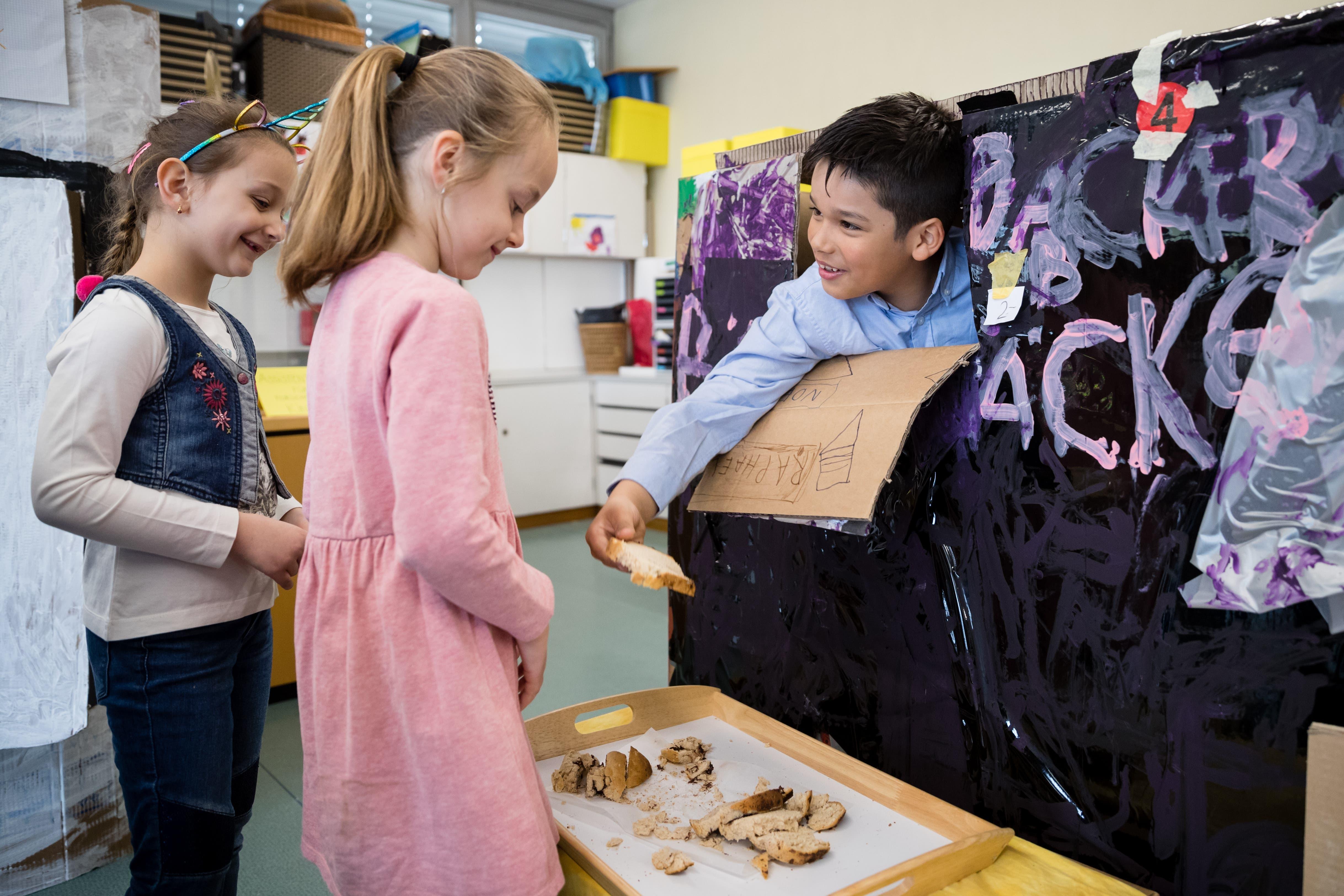 Gegen Papiergeld erhalten die Kinder in der «Bäckerei» ein Stück des selbstgebackenen Brotes. (Bild: Philipp Schmidli, Emmen, 11. April 2019)