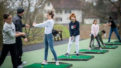 Unter fachkundiger Anleitung durch Ian Gibbons lernen die Kinder auf der Driving Range das Golfen. (Bild: Reto Martin)