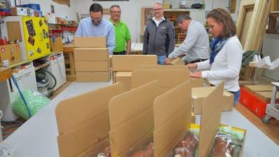 Die Kiwanis-Mitglieder verpacken die letzten Osterpäckli. Heinz Schadegg und Confiseur Stefan Bachmann schauen zu. (Bild: Mario Testa)