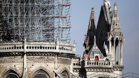 epaselect epa07508910 French firemen try to extinguish a fire as flames are burning the roof of the Notre-Dame Cathedral in Paris, France, 15 April 2019. A fire started in the late afternoon in one of the most visited monuments of the French capital.  EPA/YOAN VALAT