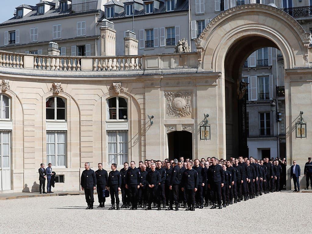Die Feuerwehrleute warteten vor dem Präsidentenpalast in der Pariser Innenstadt, bevor sie unter Applaus von Umstehenden den Hof des Gebäudes betraten. (Bild: KEYSTONE/AP/THIBAULT CAMUT)
