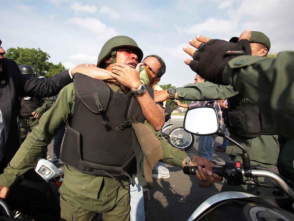Demonstranten nehmen ausserhalb des Luftwaffenstützpunktes La Carlota bei Caracas einen Maduro-treuen Nationalgardisten in den Schwitzkasten. (Bild: KEYSTONE/AP/BORIS VERGARA)