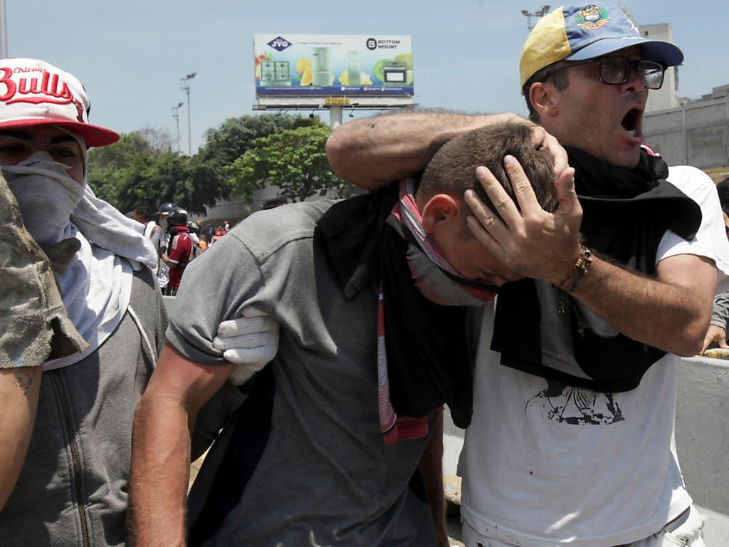 Ein verletzter Demonstrant während gewalttätigen Zusammenstössen mit der Maduro-treuen Armee in Caracas. (Bild: KEYSTONE/AP/BORIS VERGARA)