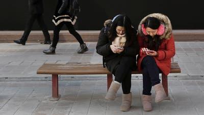 Chinesinnen konsultieren ihr Smartphone - für KP-Mitglieder nun aufgrund der neuen App auch ein politischer Akt. (Bild:Kevin Frayer/Getty; Peking, 19. Januar 2016)