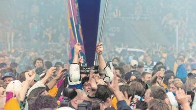 Vor fast genau 21 Jahren: Umringt von Fans stemmt ein Zuger Spieler den Meisterpokal in die Höhe. (Bild: Arno Balzarin/Keystone, Davos, 11. April 1998)