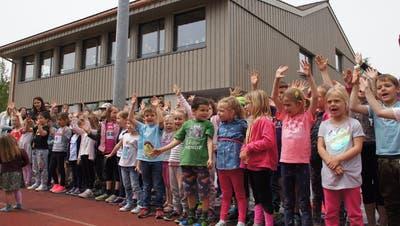 Die Kinder freuen sich über die fertiggestellte Schulraumerweiterung im Hintergrund. (Bild: Salome Preiswerk Guhl)