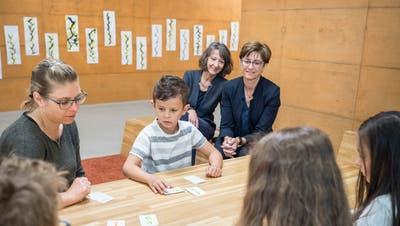 Schulpräsidentin Regina Hiller und Regierungsrätin Monika Knill schauen den Kindern über die Schulter. Bild: Andrea Stalder