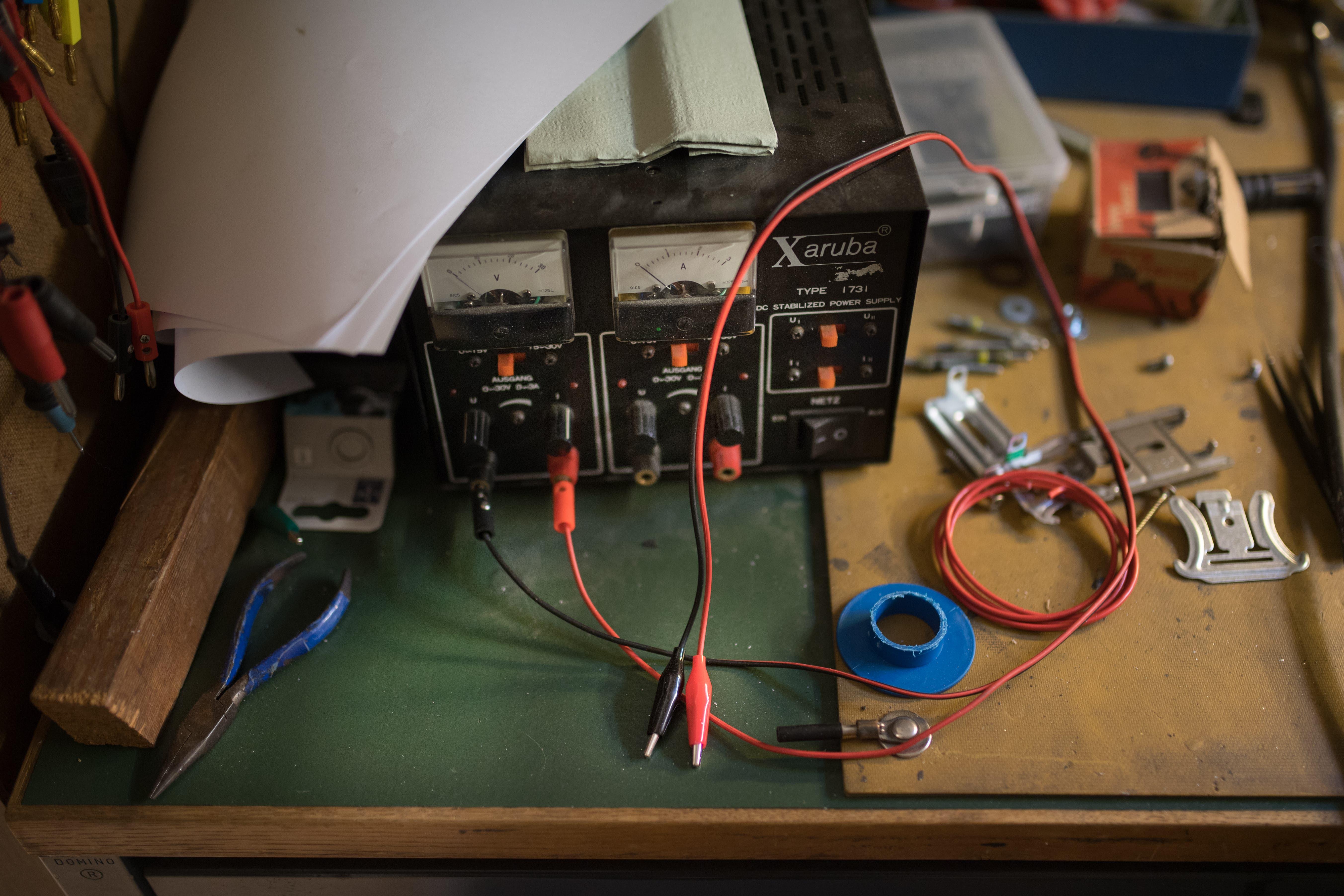 Die Werkbank hat er aus drei alten Schreibtischen improvisiert. Darauf liegen Bauteile, eine Zange und Schrauben. (Bild: Benjamin Manser)