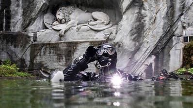 Fotografin taucht mit Kamera in Teich vor Luzerner Löwendenkmal