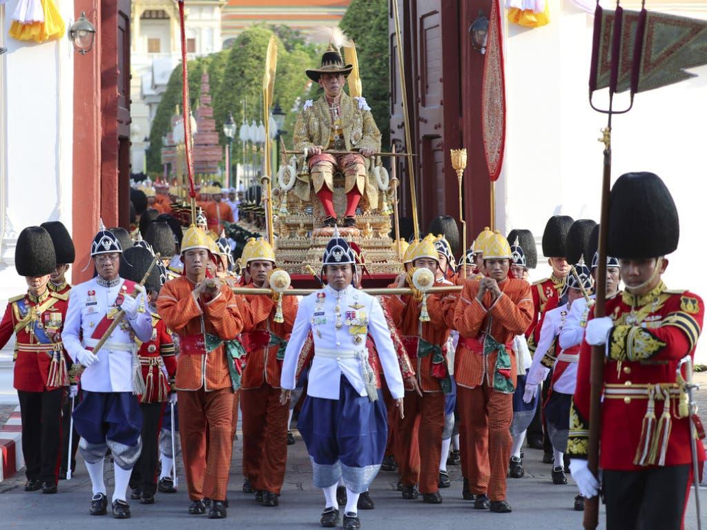 Der neu gekrönte thailändische König Maha Vajiralongkorn wird von seiner königlichen Garde auf einer Sänfte durch die Strassen der Hauptstadt Bangkok getragen. (Bild: Keystone/AP/SAKCHAI LALIT)