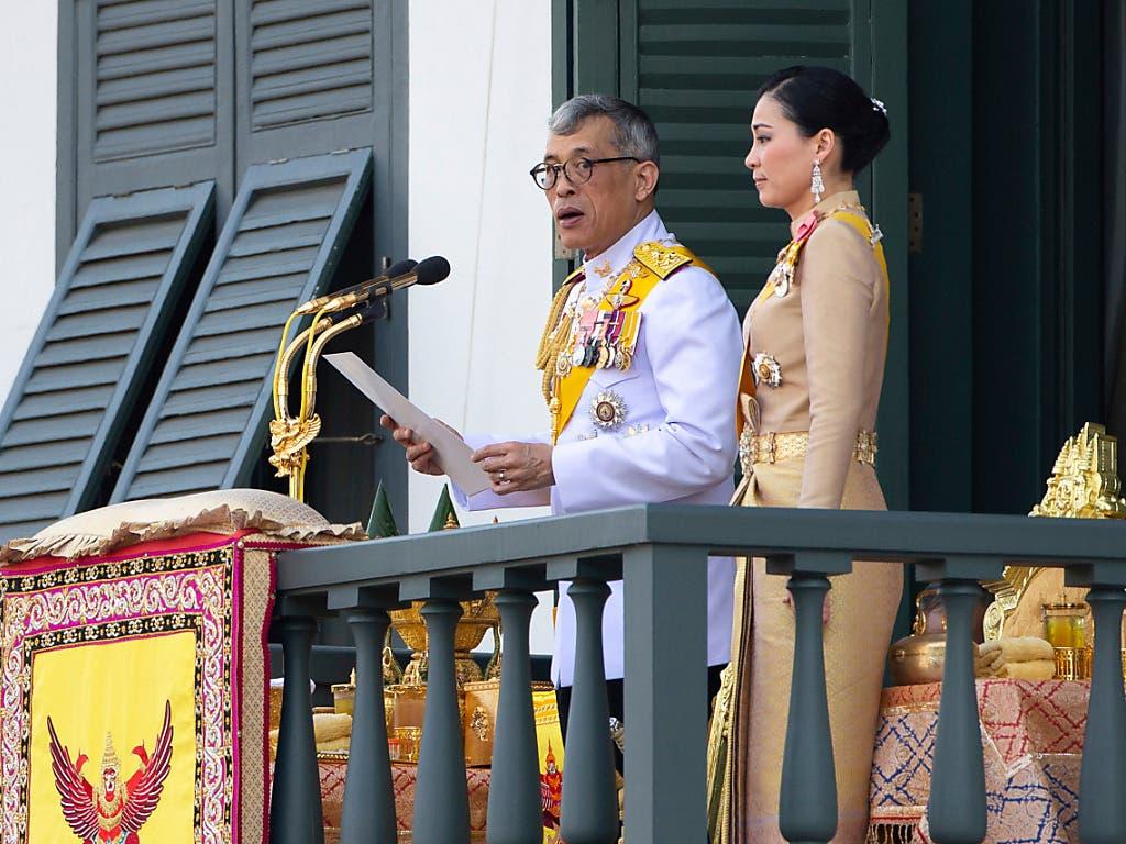 Thailands König Maha Vajiralongkorn bedankte sich am Montag in Bangkok vom Balkon des Grossen Palastes aus beim Volk für die vielen guten Wünsche. Der 66 Jahre alte Monarch und seine neue Frau, Königin Suthida (40), wurden von mehr als 40'000 Menschen bejubelt. (Bild: KEYSTONE/AP/WASON WANICHAKORN)