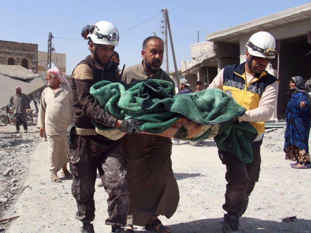 Freiwillige der Helferorganisation Weisshelme bergen ein Opfer nach Luftangriffen auf einen Markt im Dorf Ras al-Ain in der Provinz idlib. (Bild vom 7. Mai). (Bild: KEYSTONE/AP Syrian Civil Defense White Helmets)