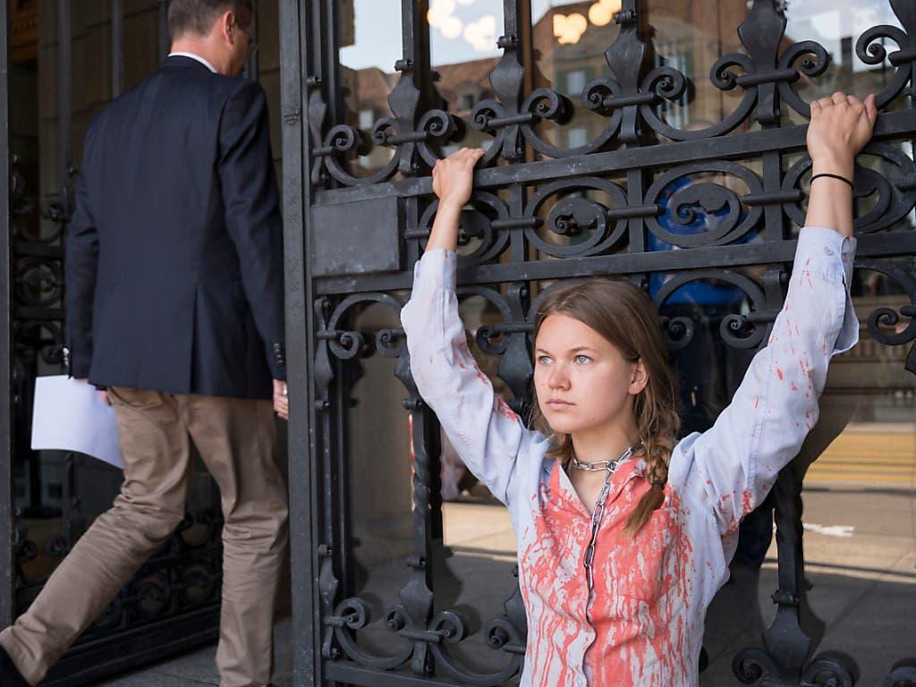 Eine Klimaaktivistin von Extinction Rebellion hat sich ans Eingangstor des Parlamentsgebäudes gekettet. (Bild: Keystone/ALESSANDRO DELLA VALLE)