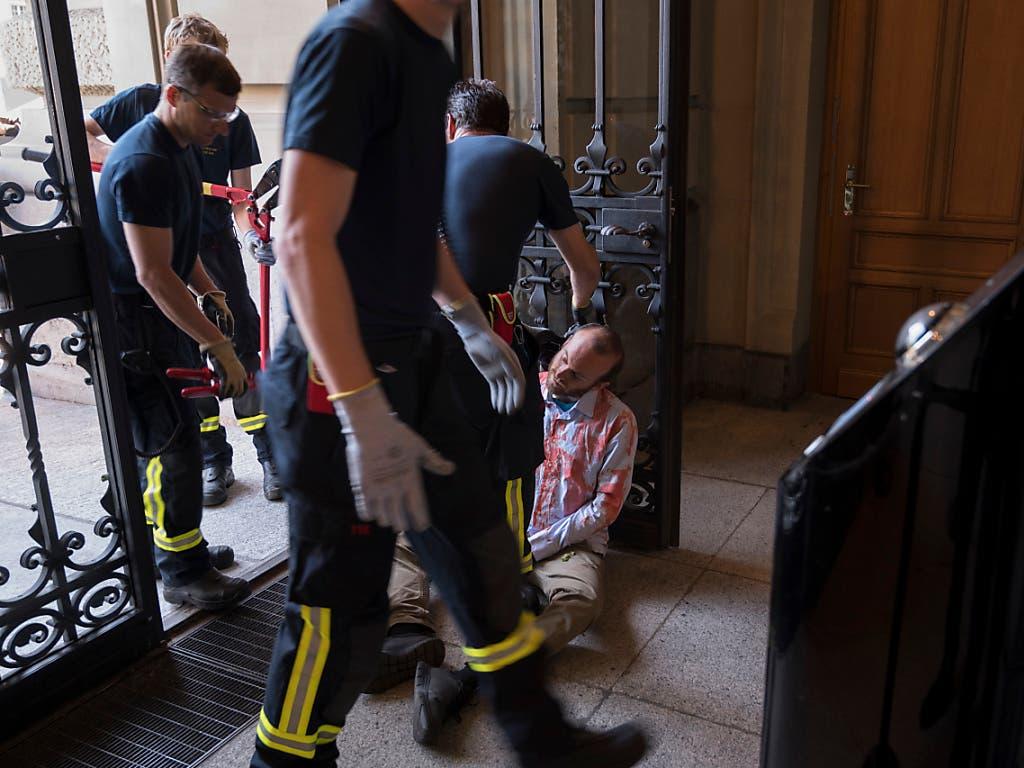 Ein Klimaaktivist von Extinction Rebellion wird von Feuerwehrleuten der Berufsfeuerwehr Bern befreit, nachdem er sich ans Eingangstor des Parlamentsgebäudes gekettet hatte. (Bild: Keystone/ALESSANDRO DELLA VALLE)