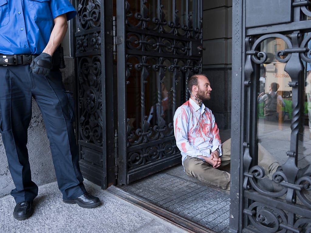 Ein Klimaaktivist von Extinction Rebellion hat sich ans Eingangstor des Parlamentsgebäudes gekettet. (Bild: Keystone/ALESSANDRO DELLA VALLE)