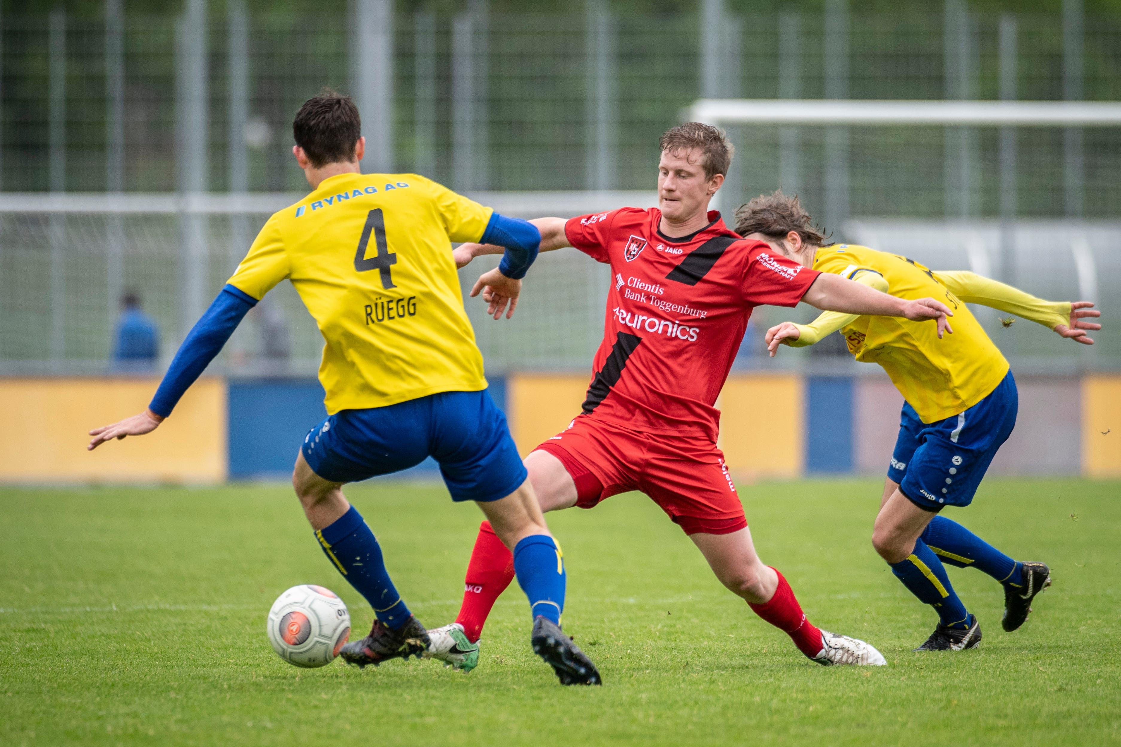 Bazenheids Mario Kuhn (im roten Trikot) muss sich im Derby gleich gegen zwei Uzwiler behaupten. (Bild: Urs Bucher/TAGBLATT)