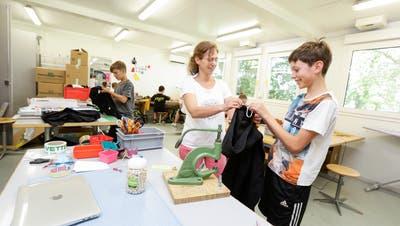 Lehrerin Maja Schäfer unterrichtet den Schülern der Halbklasse 1e im provisorisch erbauten Schulhaus Textiles Werken. (Bilder: Donato Caspari)