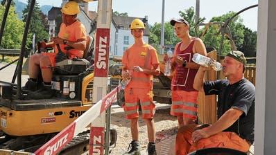 In Rorschach gehen Bauarbeiter mit Schirm am Bagger gegen Hitze vor