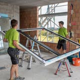 Mitarbeitende der Edelweiss Fenster AG bauen ein Fensterein. (Bild: PD)
