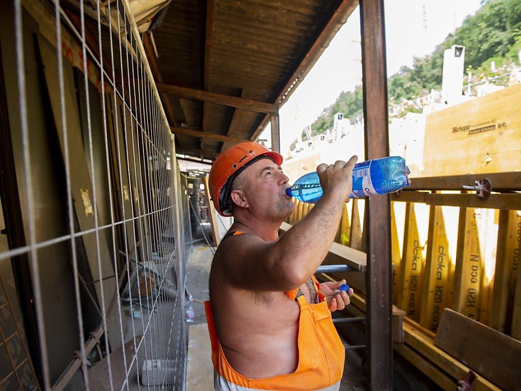 Viel trinken: Ein Arbeiter auf einer Strassenbaustelle im Tessin versorgt sich mit Wasser. (Bild: KEYSTONE/FRANCESCA AGOSTA)