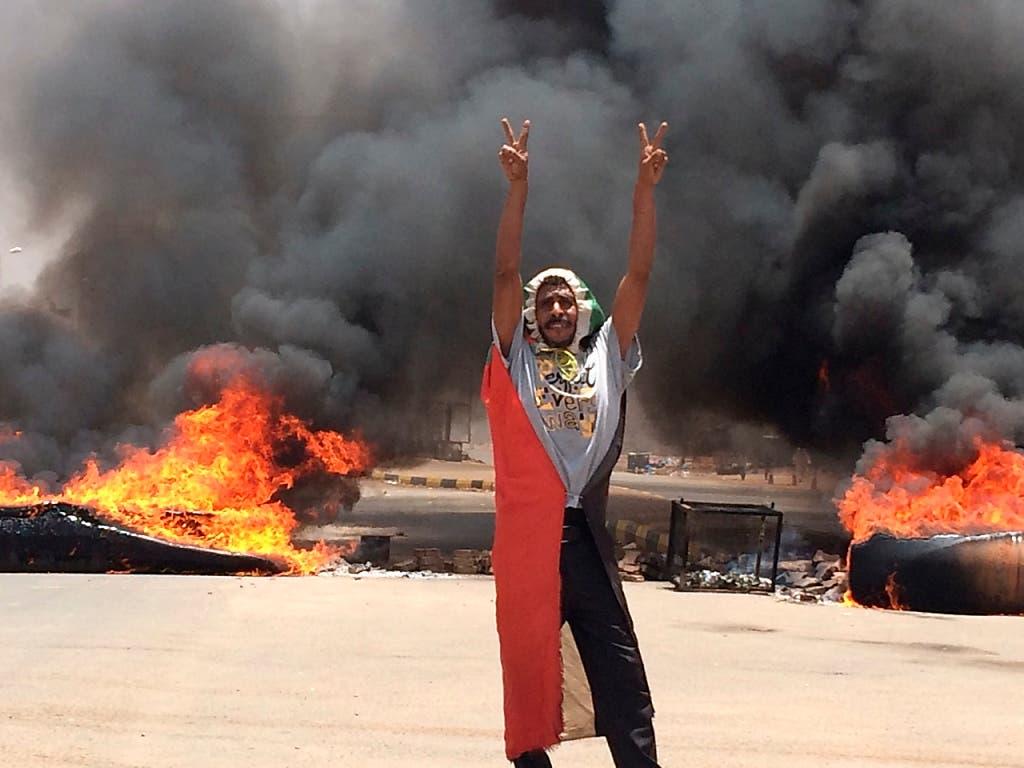 Ein Demonstrant in Khartum macht das Victory-Zeichen vor brennenden Reifen. (Bild: KEYSTONE/AP)