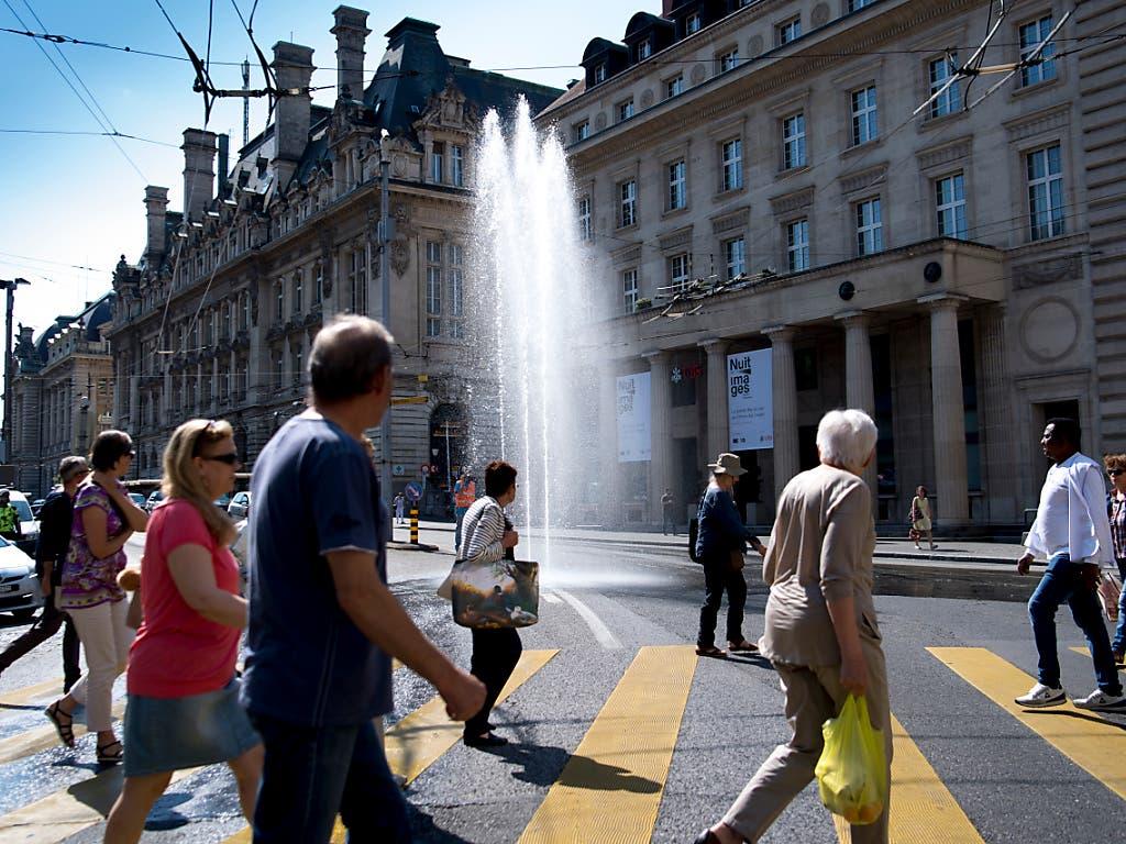 Die Passanten staunen am Mittwoch, dass bei der Place Saint-François drei Fontänen aus dem Boden schiessen. Der Verkehr wird durch die Springbrunnen nicht gestört, wie die Veranstalter versichern. (Bild: KEYSTONE/LAURENT GILLIERON)