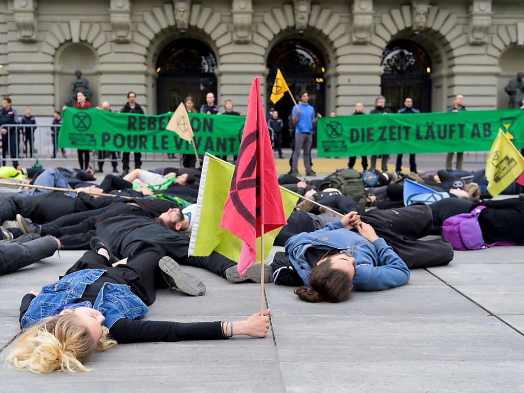 Aktivisten legten sich am Donnerstag auf den Bundesplatz um gegen die Umweltzerstörung zu protestieren. (Bild: KEYSTONE/ANTHONY ANEX)