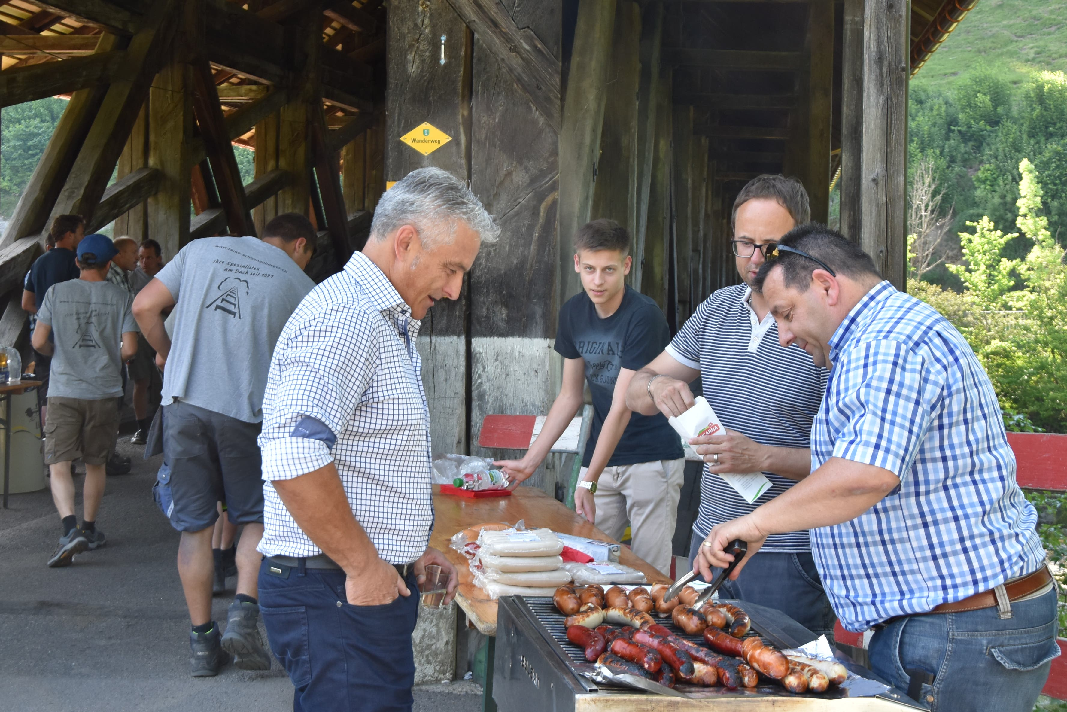 Gemeinderat Heinz Grob lässt sich von seinem Ratskollegen Ruedi Epper am Grill bedienen. (Bild: Timon Kobelt)