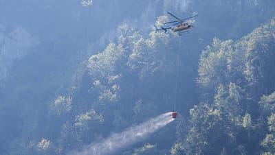Ein Helikopter transportiert Löschwasser um den Brandherd nach demKleinflugzeugabsturz am Lopper in Hergiswil. (Bild: KEYSTONE/Urs Flüeler)