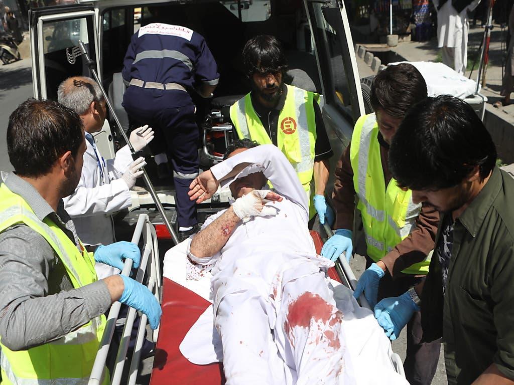 Afghanische Rettungskräfte bringen nach einem Autobombenanschlag einen Verletzten in einen Krankenwagen. (Bild: KEYSTONE/EPA/JAWAD JALALI)