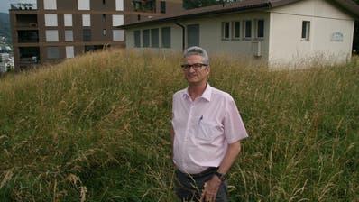 Der Horwer Gemeinderat Robert Odermatt (SVP) auf der Baurechtsparzelle, hinter ihm der leerstehende Kindergarten-Pavillon und eines der vier bestehenden Häuser der Überbauung Stirnrütipark. (Bild: Roman Hodel, Horw 8. Juli 2019)