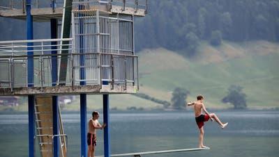 Nicht alle Besucher des Freibadshalten sich wie diese zwei Buben an das Verbot, von der Fünfmeterplattform ins Wasser zu springen. Bild: Stefan Kaiser (Oberägeri, 9. Juli 2019)