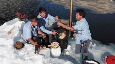 Othmar Monn, Bruno Leuzinger und Beat Walker (von links) machen Fondue auf dem kleinen Holzofen und stossen mit Weisswein an. (Bild: PD)